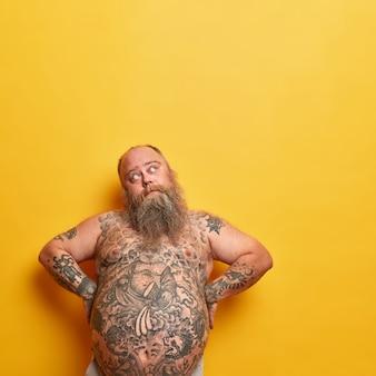 Gruby, zamyślony mężczyzna trzyma się za ręce jak okrakiem, ma duży, nagi, wytatuowany brzuch, gęstą brodę, patrzy zamyślony w górę, ma poważny wyraz twarzy, myśli, jak schudnąć, odizolowany na żółtej ścianie