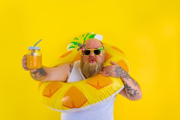 Gruby zdumiony mężczyzna z peruką w głowie jest gotowy do pływania z ratownikiem w kształcie pączka