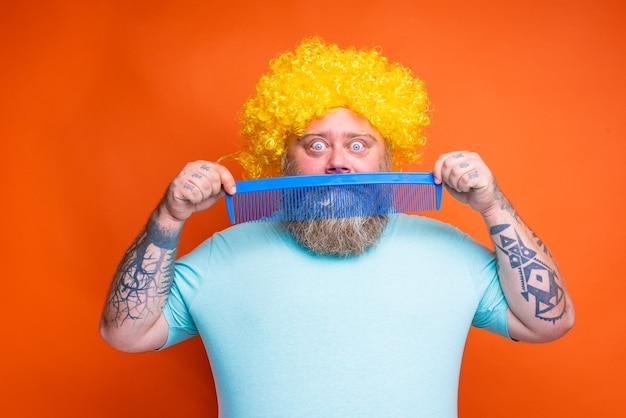 Gruby zdumiony mężczyzna z tatuażami na brodzie i okularami przeciwsłonecznymi czesze się gigantycznym grzebieniem