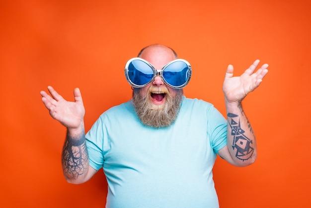 Gruby zdumiony mężczyzna z tatuażami na brodzie i okularami przeciwsłonecznymi jest szczęśliwy z czegoś