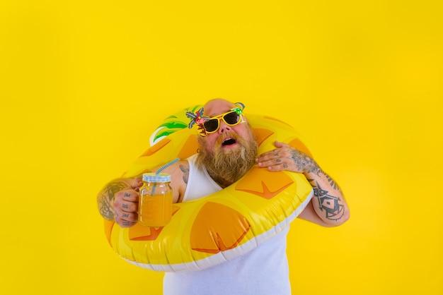 Gruby zirytowany mężczyzna z peruką w głowie jest gotowy do pływania z ratownikiem w kształcie pączka