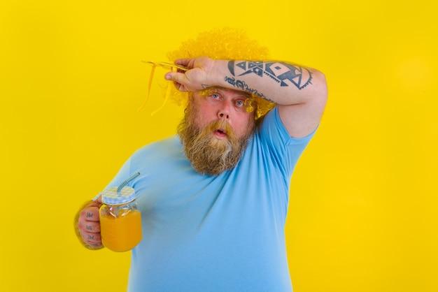 Gruby, zmęczony mężczyzna z peruką na głowie i okularami przeciwsłonecznymi pije sok owocowy