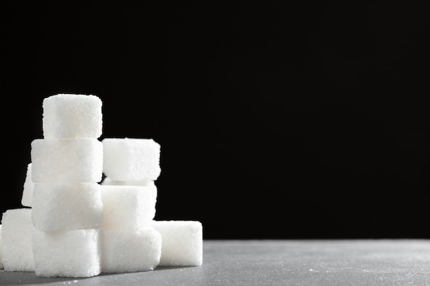 Grudki cukru ułożone razem na czarnym tle