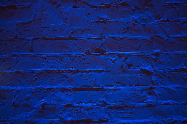 Grunge ściana z cegieł tekstury neonowy błękitny tło.