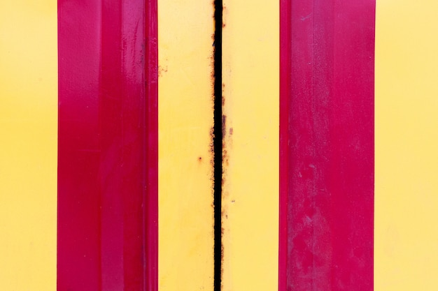 Grunge stalowe drzwi z żółtymi i czerwonymi pionowymi paskami. korozja metalu na metalowych obrzeżach.