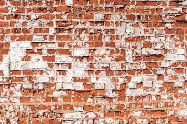 Grunge tekstury opuszczonej ściany budynku z czerwonej cegły pokrytej białym sztukaterią w jasnym słońcu ekstremalne zbliżenie. tradycyjny styl architektoniczny