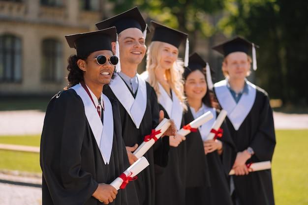 Grupa absolwentów w sukniach dyplomowych stojących obok siebie
