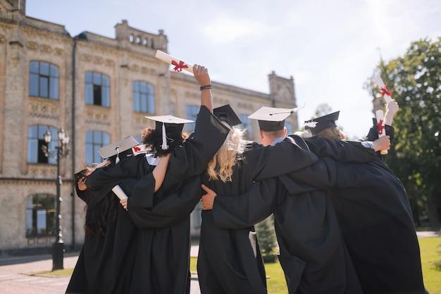 Grupa absolwentów w sukniach i czapkach, przytulających się do siebie