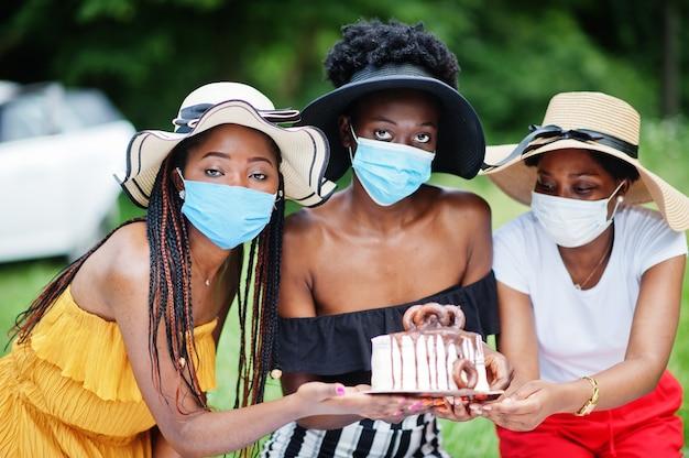 Grupa afroamerykanek z maseczkami na twarz świętuje urodziny na świeżym powietrzu z wystrojem podczas pandemii koronawirusa.