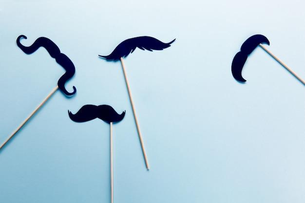 Grupa akcesoriów w postaci czarnych wąsów na sztyftach na szaro-niebieskim kolorze z miejsca na kopię.