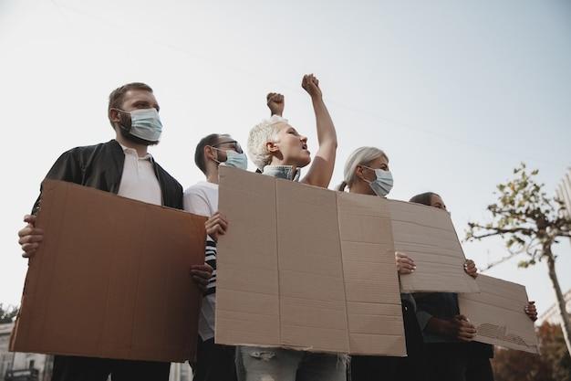 Grupa aktywistów wygłaszających hasła na wiecu mężczyzn i kobiet maszerujących razem w proteście w