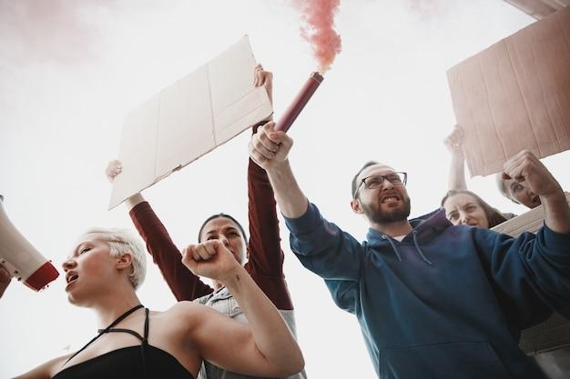 Grupa aktywistów wygłaszających hasła w wiecu kaukaskich mężczyzn i kobiet maszerujących razem