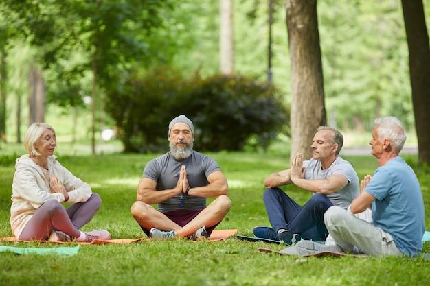 Grupa aktywnych seniorów spędzających razem słoneczny poranek w parku medytując z rękami w namaste
