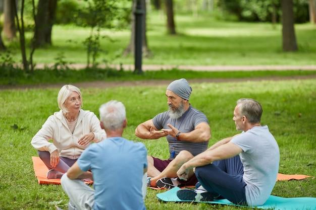 Grupa aktywnych seniorów zebrała się w parku miejskim siedząc na matach i słuchając trenera jogi