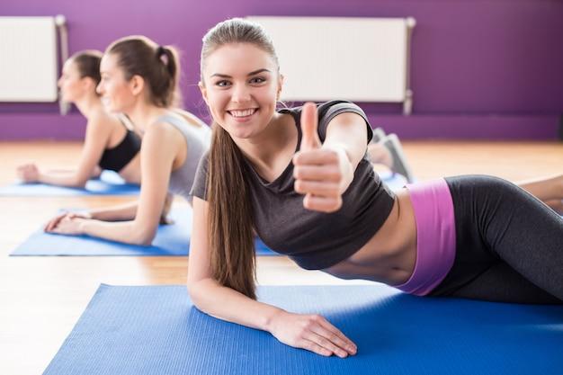 Grupa aktywnych uśmiechniętych kobiet trenuje w klubie fitness.