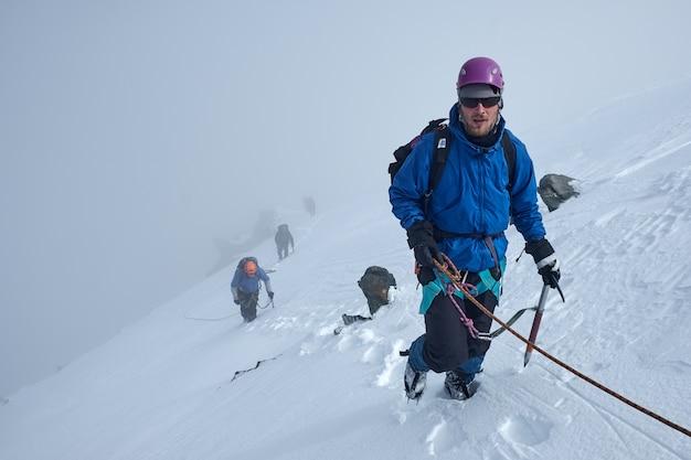Grupa alpinistów wspina się lub alpinistów na szczyt ośnieżonej góry