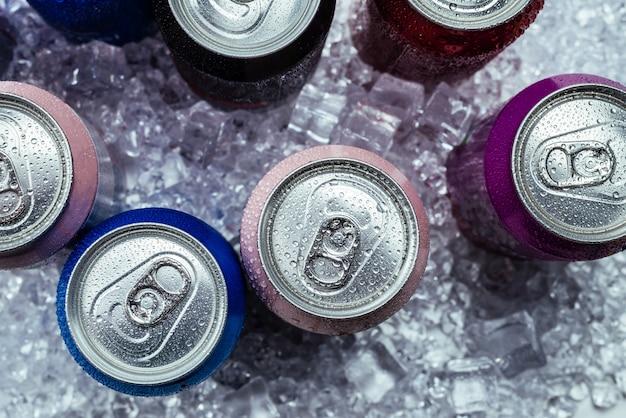 Grupa aluminiowych puszek w lodzie, zimny napój. widok z góry.