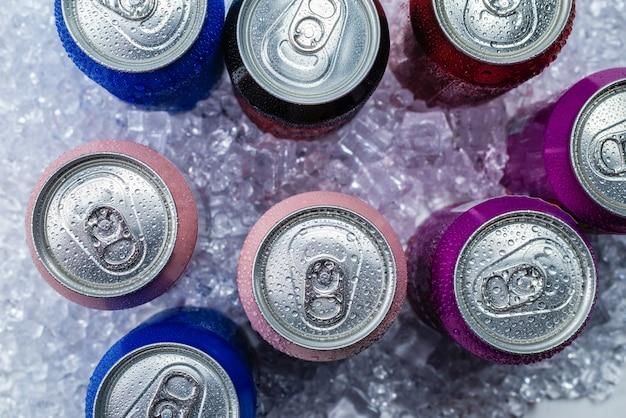 Grupa aluminiowych puszek w lodzie, zimny napój.