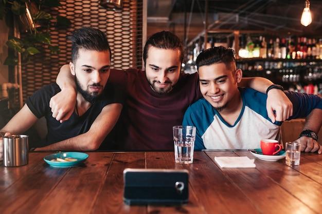 Grupa arabskich przyjaciół robi selfie w barze?