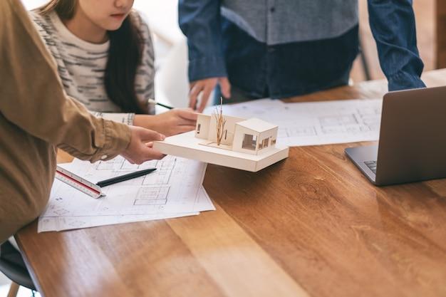 Grupa architekta pracująca i dyskutująca o modelu architektury wraz ze sklepowym rysunkiem na stole w biurze