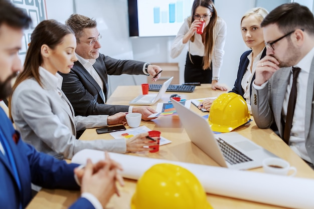 Grupa architektów, którzy odnieśli sukces, siedząc w sali konferencyjnej i omawiając nowy projekt.