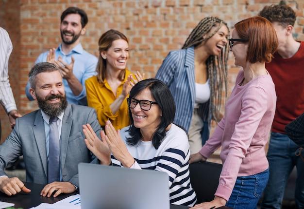 Grupa architektów przedsiębiorców śmiejących się w biurze, pracujących nad projektem.
