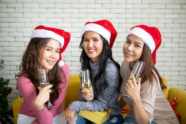 Grupa asia dziewczyna w kostiumu sezonu zimowego pije szampana dla świętować w przyjęciu bożonarodzeniowym, patrzeć z bliska zapraszam do przyłączenia się