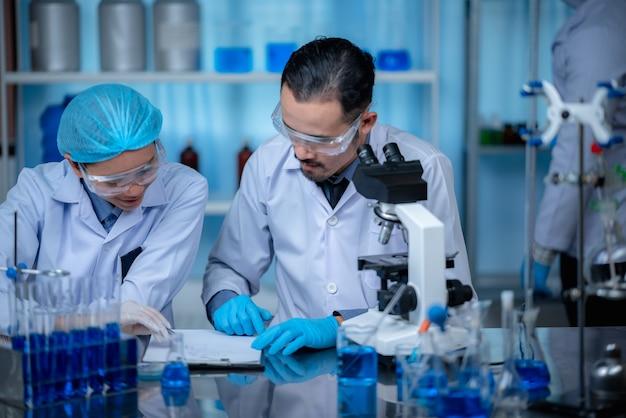 Grupa asystentów laboratoryjnych sprawdzających krew pod mikroskopem i wykonujących testy na obecność bakterii