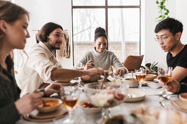 Grupa atrakcyjnych międzynarodowych przyjaciół siedzi przy stole pełnym jedzenia i spędza czas w przytulnej kawiarni