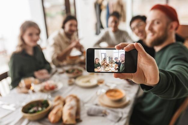 Grupa atrakcyjnych międzynarodowych przyjaciół siedzi przy stole z jedzeniem, spędzając razem czas