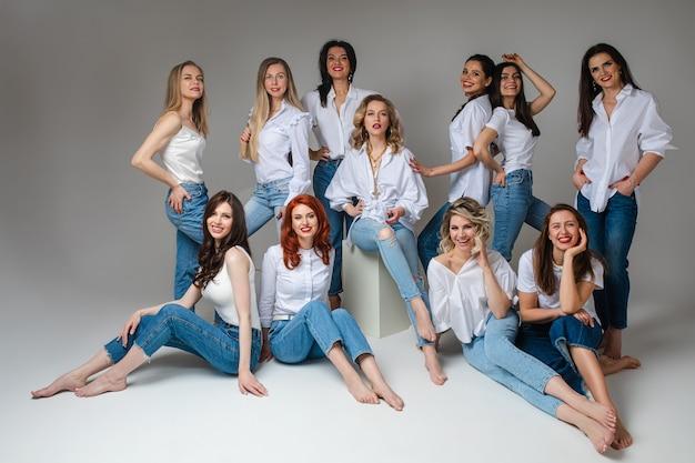 Grupa atrakcyjnych młodych dorosłych kobiet na sobie niebieskie dżinsy i biały top, uśmiechając się z przodu pozowanie