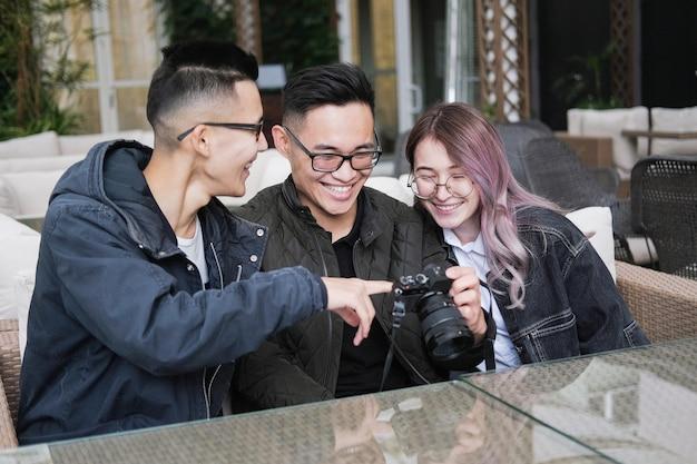 Grupa azjatów siedzą w kawiarni i oglądają zdjęcia z aparatu fotograficznego