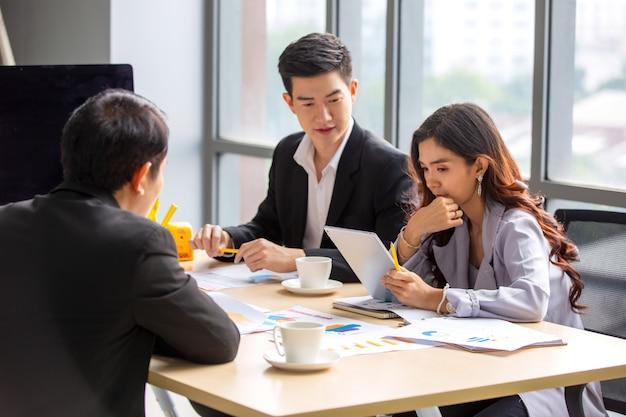 Grupa azjatyccy ludzie biznesu zespala się spotkania w nowożytnym biurowym pracującym projekta planowaniu i pomysłu pojęciu