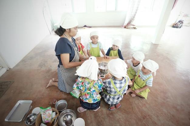 Grupa azjatyckich dzieci przygotowujących jedzenie i bawiących się w domu.
