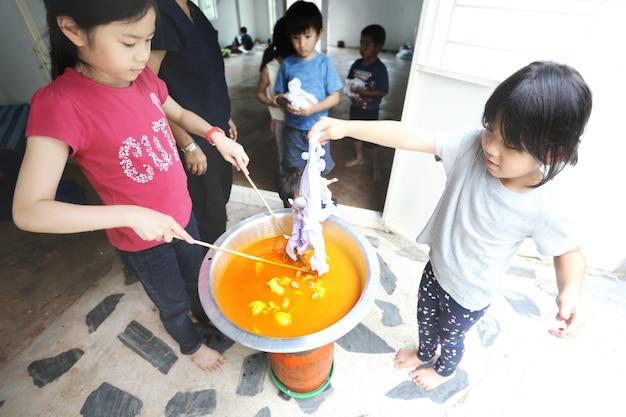 Grupa azjatyckich dzieci uczących się robić w domu farbę do krawata.