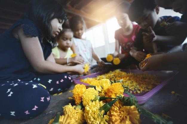 Grupa azjatyckich dzieci uczących się układania kwiatów i zabawy w domu.