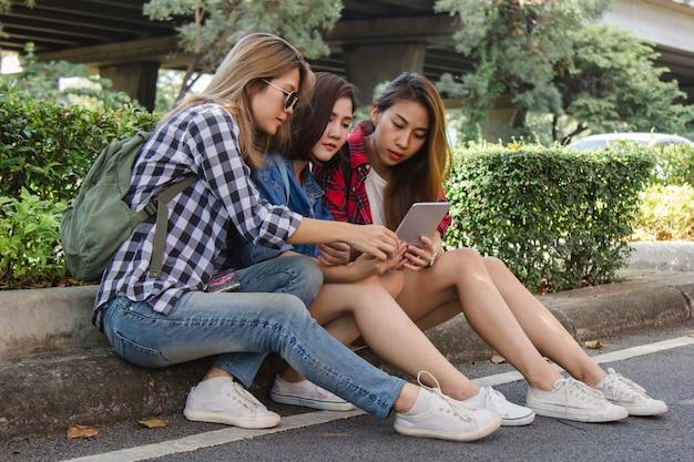 Grupa azjatyckich kobiet za pomocą smartphone dla kierunku i patrząc na mapę lokalizacji