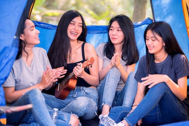 Grupa azjatyckich kobiet zabawy camping odkryty w głębokim lesie