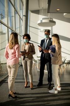 Grupa azjatyckich ludzi biznesu spotykających się i pracujących w biurze oraz noszących maski w celu ochrony przed infekcją wirusem koronowym