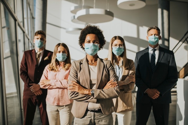 Grupa azjatyckich ludzi biznesu stojących w biurze i nosić maskę w celu ochrony zapobiec infekcji wirusem koronowym