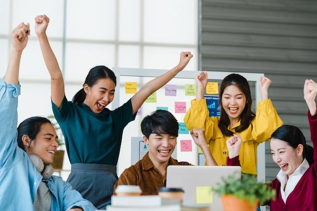 Grupa azjatyckich młodych kreatywnych ludzi w eleganckich strojach codziennych dyskutujących o biznesie świętuje dając pięć po radzeniu sobie z uczuciem szczęścia i podpisaniu umowy lub porozumienia w biurze. koncepcja pracy zespołowej współpracownika.