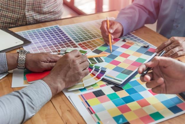 Grupa azjatyckich projektantów przeprowadzająca burzę mózgów współpracująca z kolegami i próbkami kolorów