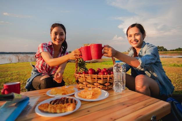 Grupa azjatyckich przyjaciół pijących kawę i spędzających czas na pikniku podczas letnich wakacji. są szczęśliwi i bawią się na wakacjach.