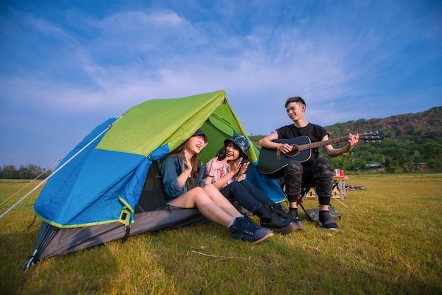 Grupa azjatyckich przyjaciół turystów pijących i grających na gitarze razem ze szczęściem w lecie podczas biwakowania nad jeziorem o zachodzie słońca