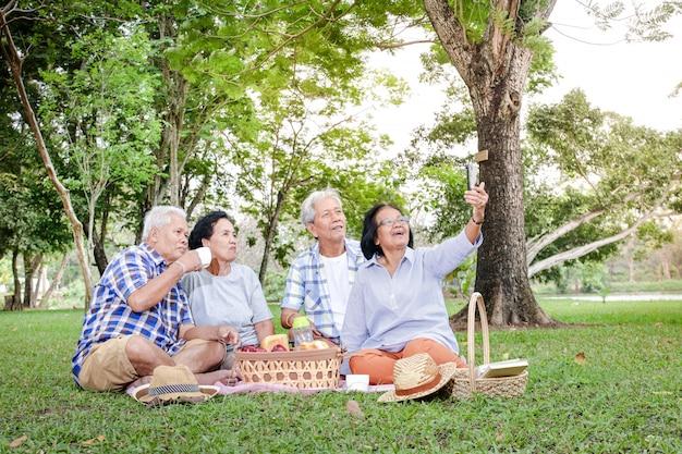 Grupa azjatyckich seniorów siedzi, odpoczywa i przygotowuje jedzenie do zjedzenia w zacienionym ogrodzie.