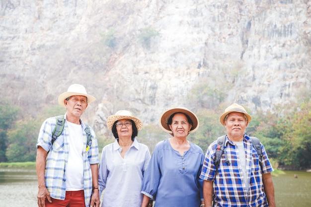 Grupa azjatyckich seniorów wędrujących i stojących w wysokich górach, cieszących się przyrodą