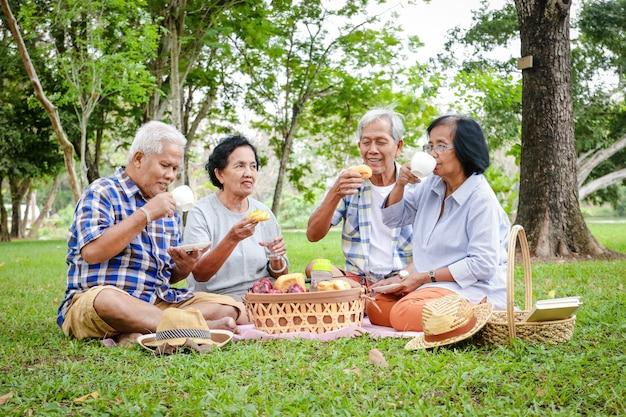 Grupa azjatyckich starszych siedzi, odpoczywa i przygotowuje przekąski do jedzenia w zacienionym ogrodzie. oglądaj ich szczęśliwych. koncepcje społeczności osób starszych. piknik w parku