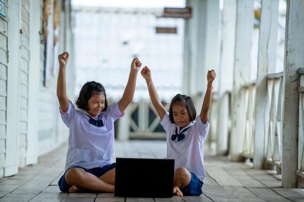 Grupa azjatyckich uczniów szkół podstawowych, którzy razem uczą się korzystać z laptopa w klasie
