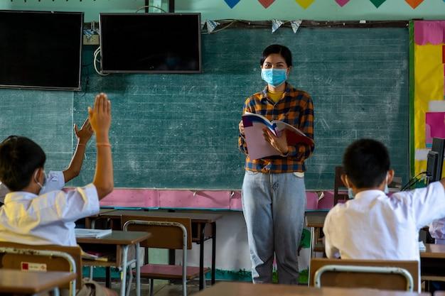 Grupa azjatyckich uczniów szkół podstawowych noszących maskę ochronną w celu ochrony przed covid-19, uczniowie w mundurach z nauczycielem uczącym się razem w klasie