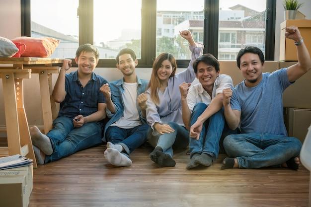 Grupa azjatyckiej pracy zespołowej cieszy się po pomyślnym zapakowaniu dużego kartonowego pudła